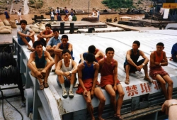 Another view of the young Chinese dock workers in their multi-colored t-shirts.