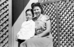 Paul with Mom outside house in Chinatown, 1949.