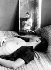 Paul at home in bedroom with reflection of Joan Cuadra.